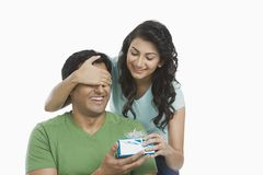 Woman giving a gift to her husband Stock Image