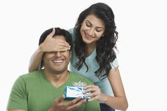 Woman giving a gift to her husband Stock Photos