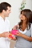 Woman giving a gift to a man Royalty Free Stock Images