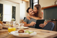 Woman giving good morning kiss to her boyfriend in kitchen. Young men holding a digital tablet while his girlfriend hugs him from behind, giving him a good Royalty Free Stock Photography