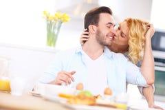 Woman giving good morning kiss to her husband Stock Image