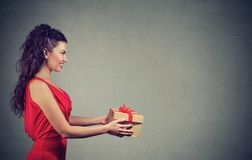 Woman giving a great present. Beautiful young woman giving a great present holding a box royalty free stock image