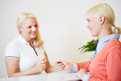 Woman giving health card to doctors assistant Stock Images