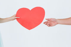 Woman giving heart card to her boyfriend. On white background Royalty Free Stock Photo