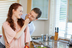 Woman giving her boyfriend some bell pepper Stock Photos