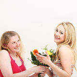 Woman giving her friend a bouquet Stock Photography