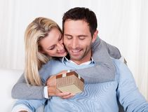 Woman giving her husband a surprise gift Stock Images