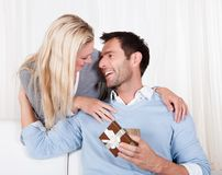 Woman giving her husband a surprise gift. Smiling beautiful women leaning over her husband's shoulder giving him a surprise gift Stock Photos