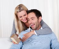 Woman giving her husband a surprise gift Royalty Free Stock Photos