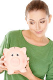 Woman giving her piggy bank a speculative look Royalty Free Stock Photo