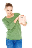 Woman giving her piggy bank a speculative look Royalty Free Stock Photography
