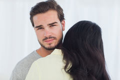 Woman giving hug to uninterested boyfriend Royalty Free Stock Photography