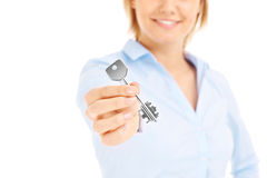 Woman giving key. Young woman giving key over white background Stock Photography