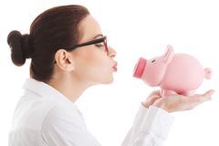Woman giving a kiss to her piggybank Royalty Free Stock Images