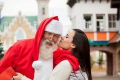 Woman giving a kiss to santa claus Royalty Free Stock Photo