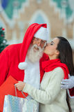 Woman giving a kiss to santa Royalty Free Stock Photos