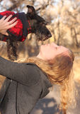 Woman Giving a Kiss to Scottish Terrier Dog. Woman holding her Scottish Terrier Dog giving him a kiss Royalty Free Stock Photos