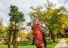 Woman giving little boy piggyback ride smiling Royalty Free Stock Images