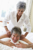 Woman giving man massage in bedroom smiling Royalty Free Stock Photos