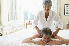 Woman giving man massage in bedroom smiling. Woman giving man a massage in the bedroom royalty free stock images