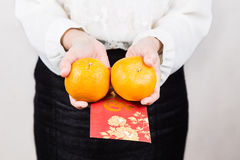 Woman giving mandarin oranges, red envelop with Good Luck charac. Perspective view of woman giving mandarin oranges and red envelop with Good Luck character, a Royalty Free Stock Image