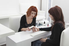 Woman Giving Manicure To Customer In Hairdressing Salon Stock Image