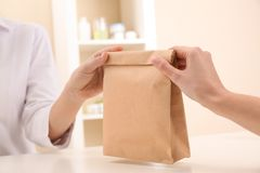 Woman giving paper bag with order to customer in shop, closeup. Mock up for design stock image