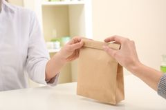 Woman giving paper bag with order to customer in shop, closeup. Mock up for design stock photo