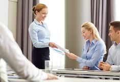 Woman giving papers to group of businessmen Stock Photos
