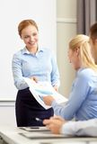 Woman giving papers to group of businessmen Royalty Free Stock Images