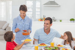 Woman giving pasta sauce to her son Stock Photo