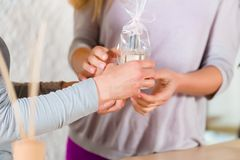 Woman giving perfume gift to her friend royalty free stock photography