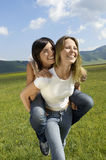 Woman Giving Piggyback Ride To Friend In Park Stock Image