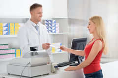 Woman Giving Prescription To Pharmacist Royalty Free Stock Photo