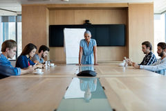 Woman giving presentation to her colleagues in conference room Royalty Free Stock Photography