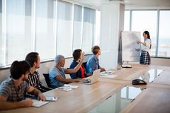 Woman giving presentation to her colleagues in conference room. At office Royalty Free Stock Images