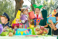 Woman giving presents to children. Woman giving present to children during garden costume party Stock Image