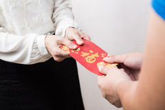Woman giving red envelop with Good Luck character in Chinese Stock Image