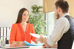 Woman giving resume in a job interview. Woman giving a resume to the interviewer in a job interview Royalty Free Stock Images