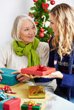 Woman giving senior gift for christmas Stock Photos