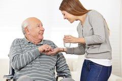 Woman giving senior man Stock Photo