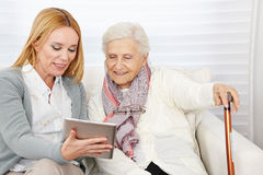 Woman giving senior woman Stock Images