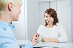 Woman giving smartcard to receptionist Royalty Free Stock Photo