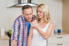 Woman giving something to eat at her husband. In the kitchen Stock Photos