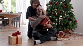 Woman giving surprise christmas gift to man. Young woman closing eyes of her man and giving a surprise christmas gift. Happy young couple with a present sitting stock video footage