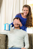 Woman giving a surprise gift to her man Royalty Free Stock Photos