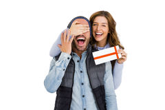Woman giving a surprise gift to her man. Woman covering mans eyes while giving him a surprise gift on white background Stock Images