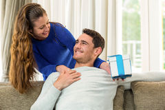 Woman giving a surprise gift to her man Stock Image