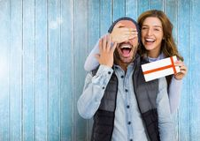 Woman giving surprise gift to man Stock Images