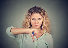Woman giving thumb down gesture looking with negative expression. And disapproval  on gray background Royalty Free Stock Photo